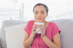 Peaceful woman enjoying a coffee break on the sofa. At home Stock Photos
