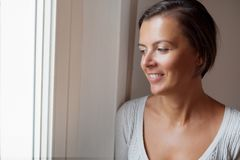 Peaceful woman looking out the window Stock Photos