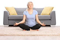 Peaceful woman meditating seated on the floor Stock Images