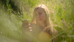Peaceful woman relaxing in the beautiful sunny outdoors looking at the smart phone stock video