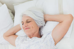 Peaceful woman relaxing in bed Stock Photography