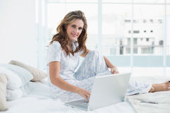 Peaceful woman sitting on cosy bed using laptop Royalty Free Stock Photography