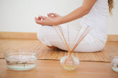 Peaceful woman sitting in lotus pose on bamboo mat Royalty Free Stock Image