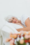 Peaceful woman sleeping in bed Stock Photography