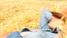 Peaceful woman wearing cowboy hat lying in hay Stock Photo