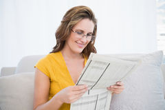 Peaceful woman wearing glasses reading newspaper Stock Photo