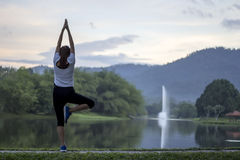Peaceful women yoga exercise in front of pond Royalty Free Stock Photography