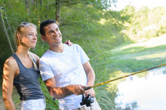 Peaceful young couple fishing by pond Royalty Free Stock Photos