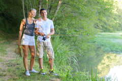 Peaceful young couple fishing by pond Stock Photography