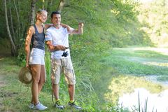 Peaceful young couple fishing by pond in autumn Royalty Free Stock Photography