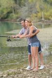 Peaceful young couple fishing by pond in autumn Royalty Free Stock Image