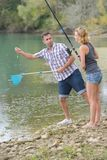 Peaceful young couple fishing by pond Royalty Free Stock Images