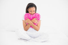 Peaceful young dark haired model cuddling a heart-shaped pillow Stock Images