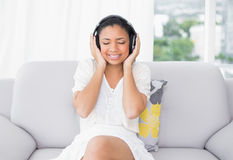 Peaceful young dark haired woman in white clothes listening to music Stock Photo