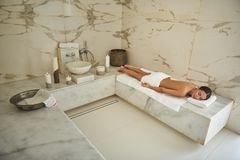 Calm young lady closing her eyes while relaxing in hammam stock photography