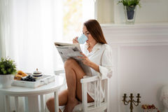 Peaceful young woman reading magazine at home. Peaceful young woman reading magazine while drinking Stock Photography