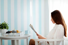 Peaceful young woman reading magazine at home. Peaceful young woman reading magazine sitting at home Royalty Free Stock Images