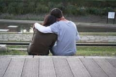 Peacefull love. Couple holding each other in the park at dusk stock photography
