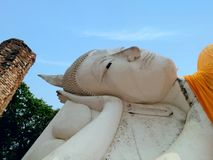 Peacefully expression of holy reclining Buddha sculpture Wat Khun Inthapramun under clear blue sky Royalty Free Stock Images