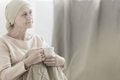 Woman with tumor. Peacefully looking woman with tumor wearing a headscarf and holding a cup of tea Stock Photo