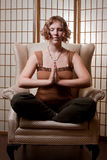 Peacefully meditating. A pretty young lady sits meditating on an armchair Royalty Free Stock Image