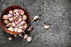 Peaces of fresh garlic in a wooden bowl. On a rustic background Stock Images