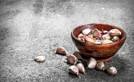 Peaces of fresh garlic in a wooden bowl. On a rustic background Stock Photos