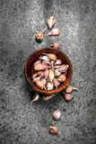 Peaces of fresh garlic in a wooden bowl. On a rustic background Stock Photography