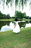 Peacful. A little toddler girl in a white dress by a pond bending over to pick something up. Beautiful scenery Royalty Free Stock Photography
