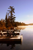 Peacful Dock. A beautiful morning vista overlooking bearskin lake.  There is a fog on the lake, and lots of reflections, along with some docks with outdoor Royalty Free Stock Photography