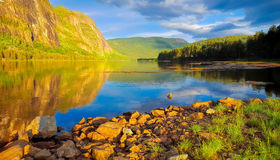 Peacful lake on a warm summer day. Peaceful lake, trees and sunset at Setesdalen, Norway Stock Photo