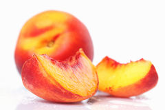 Peach. One peach an two slices with water drops shot on white background Stock Images