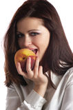 Peach. The girl eats a peach on a white background Royalty Free Stock Image