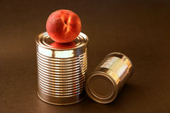 Peach and aluminum cans. Peach with two aluminum cans on brown background Royalty Free Stock Photography