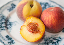 Peach on antique blue plate. royalty free stock photo