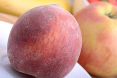 Peach,  apple and strawberry on wooden plate Royalty Free Stock Photos