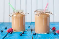 Peach and banana milkshake in mason jar with fresh. Raspberry, strawberry on the background of blue wooden boards. Selective focus Stock Photos