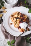 Peach and blackberries Cobbler with Coconut Cream. On wooden Background royalty free stock photography