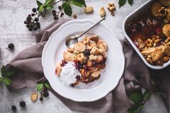 Peach and blackberries Cobbler with Coconut Cream. On wooden Background royalty free stock images
