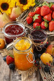 Peach, blueberry and strawberry jams in glass jars Royalty Free Stock Photography