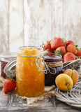 Peach, blueberry and strawberry jams in glass jars Stock Photos