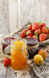 Peach, blueberry and strawberry jams in glass jars Stock Photo