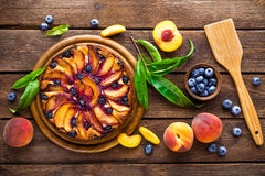 Peach cake. Peach and blueberry cake with fresh fruits and leaves Royalty Free Stock Image