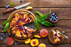 Peach cake. Peach and blueberry cake with fresh fruits and leaves Royalty Free Stock Photos