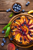 Peach cake. Peach and blueberry cake with fresh fruits and leaves Stock Photos