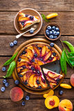 Peach cake. Peach and blueberry cake with fresh fruits and leaves Royalty Free Stock Images
