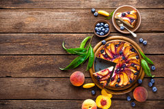 Peach cake. Peach and blueberry cake with fresh fruits and leaves Stock Images