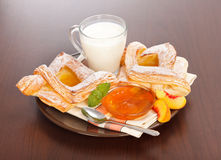 Peach cake and jam with milk for breakfast. Peach cake, jam and slices with milk on plate, for breakfast Royalty Free Stock Image