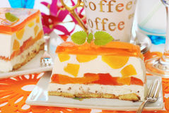Peach cake with jelly. Portion of peach cake with jelly layers and coffee Royalty Free Stock Images