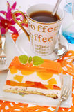 Peach cake with jelly and coffee. Portion of peach cake with jelly layers and coffee Stock Photo
